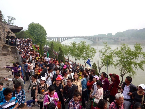 Crowds queue along banks of the Yi River