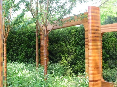 Designer Joe Swift cleverly juxtaposed a cedarwood framework with the similarly burnished & banded trunks of Prunus maackii 'Amber Beauty'