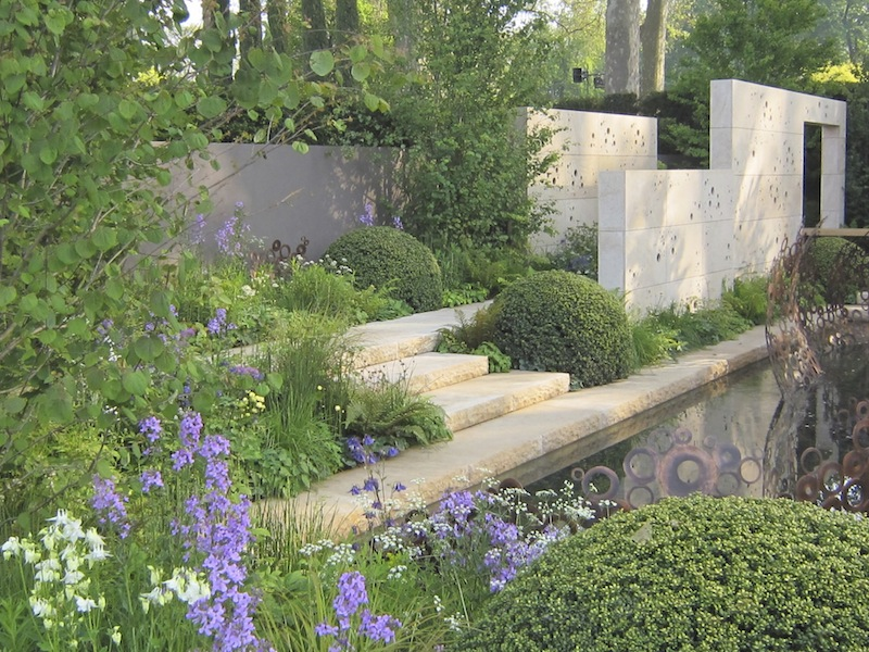 Campanula and aquilegia between balls of holly with loose cottage plants to highlight the stonework